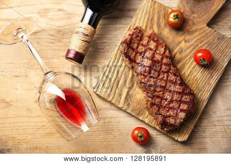 Grilled steak on cutting board with wine and cherry tomatoes, closeup