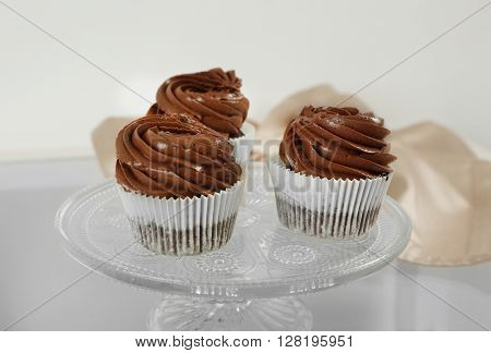 Three chocolate cupcakes on light glass background, close up