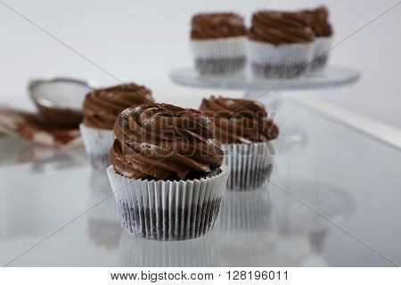 Chocolate cupcakes on light glass background, close up