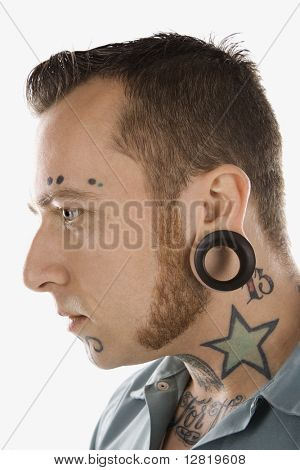 Caucasian mid-adult man with tattoos and piercings.