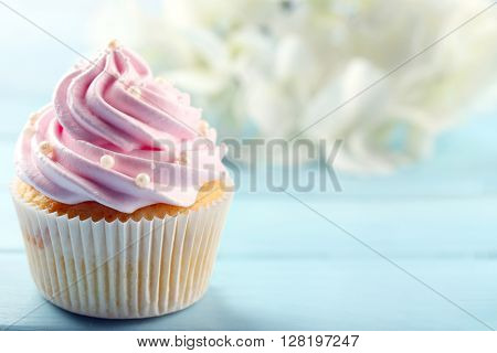 Pink cupcake on wooden background