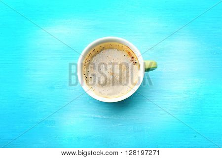 Cup of coffee on turquoise background, top view