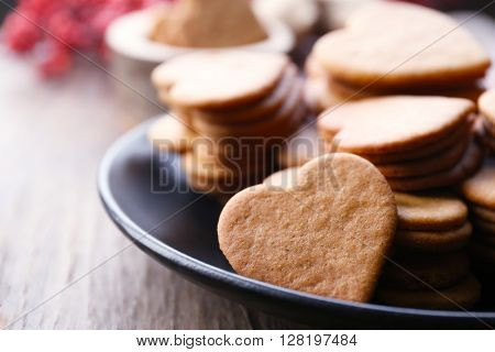 Heart shaped biscuits on plate with ash berry on wooden background