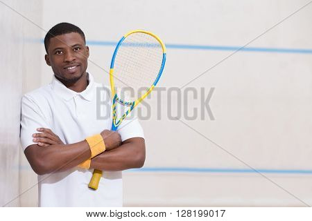 Male squash player posing for photographer isolated against white background. Happy smiling black man on squash court.