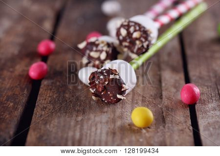 Tasty marshmallows with chocolate on sticks, on old wooden table