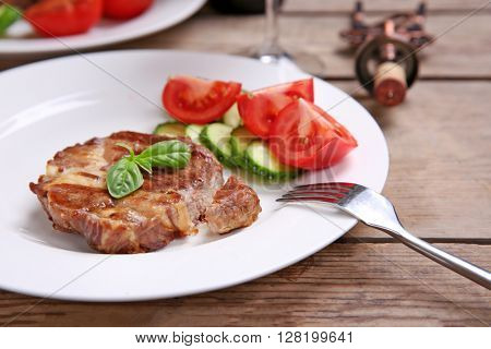 Roasted beef fillet and fresh vegetables on plate, on wooden background