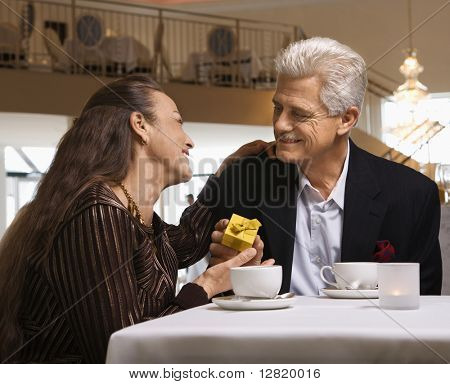 Caucasian mature adult male giving prime adult female gift box at restaurant table.