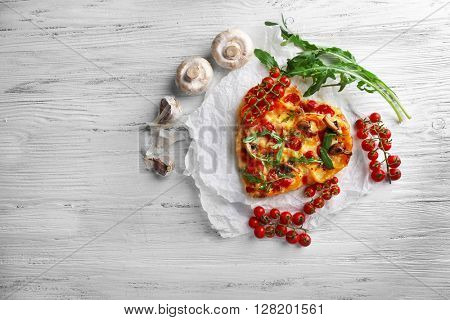 Heart shaped decorated pizza on white cotton serviette on wooden background