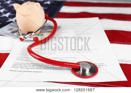 Piggy bank with stethoscope, dollar banknotes and medical form on American flag