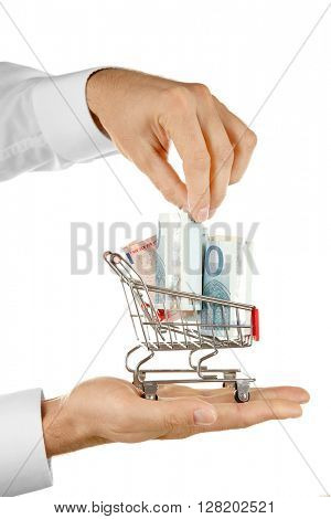 Male hands holding supermarket trolley with euro banknotes, isolated on white