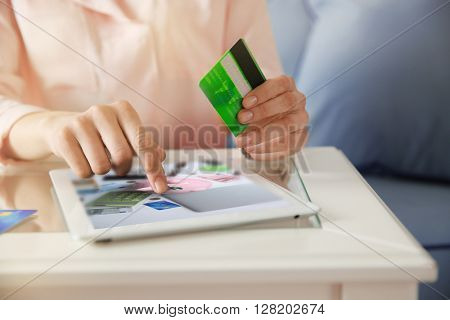 Female hands with digital tablet and credit card, closeup