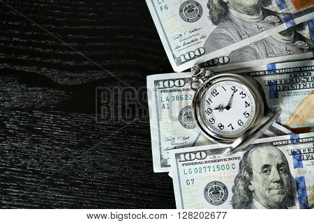 Time is money concept with pocket watch and dollars bills on wooden table, top view