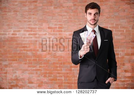 Attractive man in a suit holding fan of euro banknotes on brick wall background