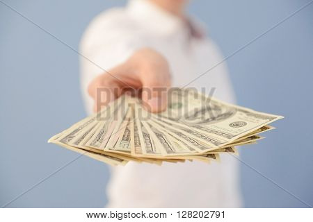 Man holding fan of dollar banknotes on blue background