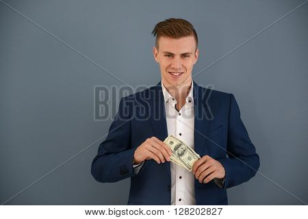 Attractive man in a suit with dollar banknotes on blue background