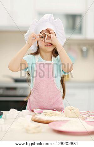 Beautiful little girl cutting hearts from a dough