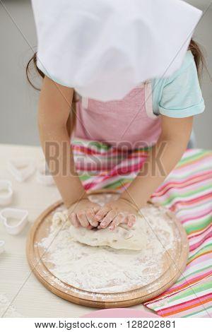 Beautiful little girl rolling the dough.