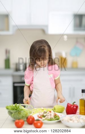 Little girl cutting mushrooms for the salad in the kitchen