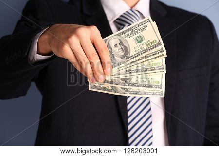 Man in a suit holding fan of dollar banknotes, close up