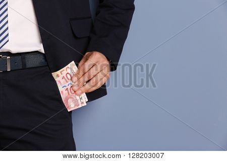 Man getting euro banknotes out of suit pocket on grey background