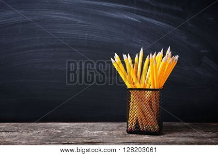 Set of pencils in metal holder on blackboard background