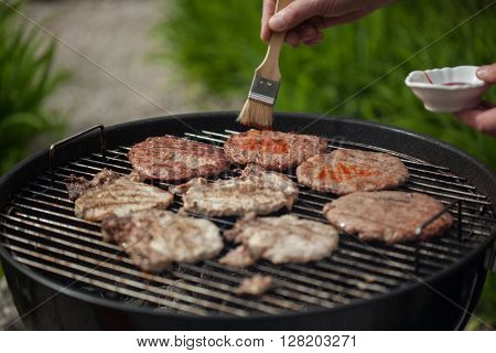 Person putting sauce on burgers