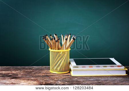 Set of pencils in metal holder, book and tablet on blackboard background