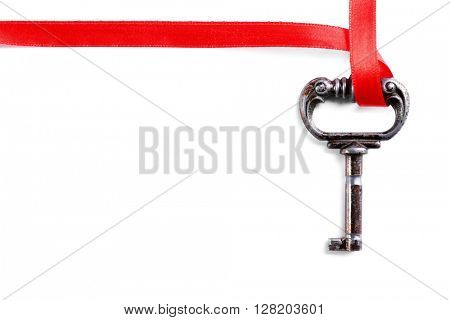 Vintage key with a red ribbon on a white background
