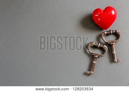 Vintage keys with a little red heart on a color background