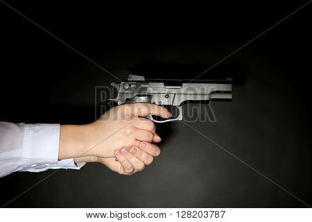 Woman holding handgun on dark lighted background