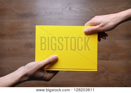 Male and female hands holding book on wooden background.