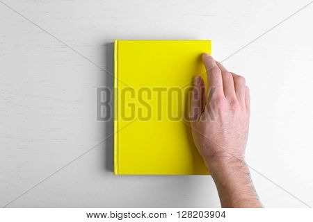Male hand hold the yellow book on white table.