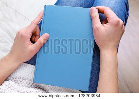 Female hands holding a blue book.