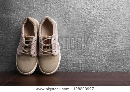 Sneakers for kid on grey textured background