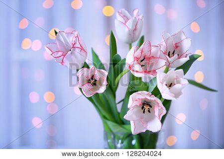 Bouquet of fresh tulips in front of window  on blurred garland light background