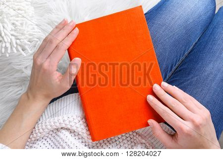 Female hands holding a red book.
