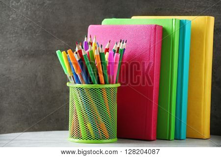Books pens and markers in metal holder on the table