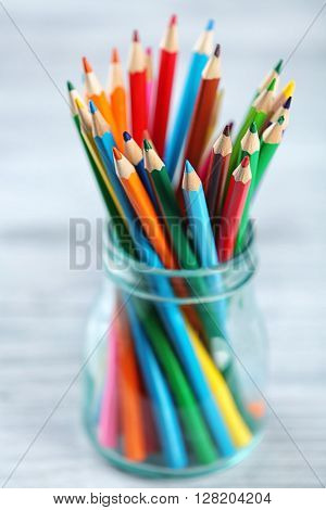 Pencils in glass jar on wooden background on blurred background