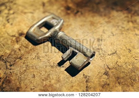 Old key on lighted background, close up