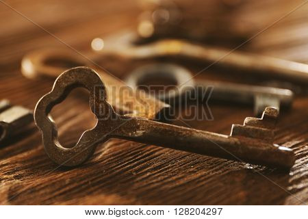 Old keys on wooden background, close up