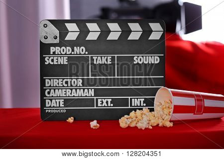 Movie clapper and popcorn on blurred background