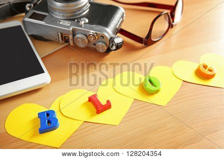 The word BLOG from colorful letters, glasses, retro camera and mobile phone on wooden background