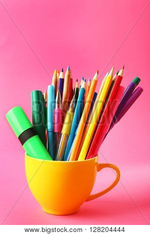 Colorful stationery in yellow cup on pink background