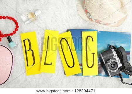 The word BLOG from cutout paper pieces with female accessories on fur background