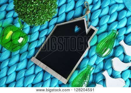 Little details of home interior on knitted blanket background, top view