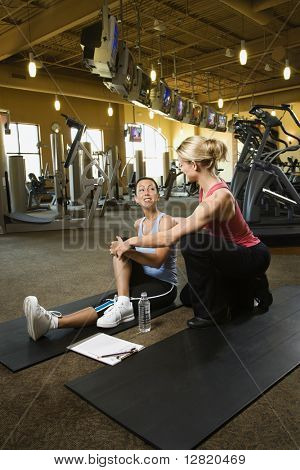 Prime adult Caucasian female with personal trainer at gym.