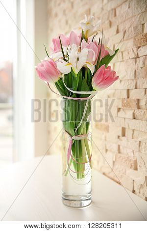 Beautiful bouquet of fresh flowers against brick wall background