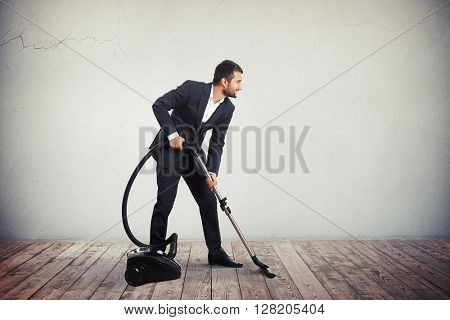 A man in dark grey business suit is cleaning the wooden floor with vacuum cleaner
