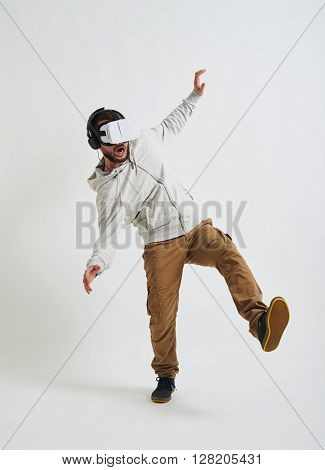 The picture in virtual reality glasses seems so real to the young man that he thinks he is falling down