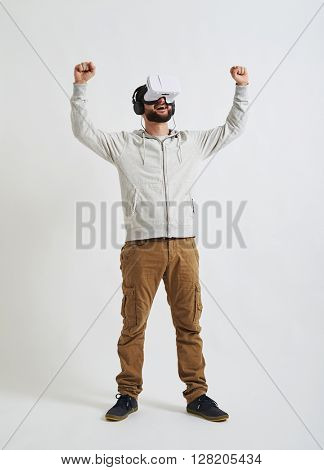 A young man in casual clothes and virtual reality glasses feels joyful in 3d reality